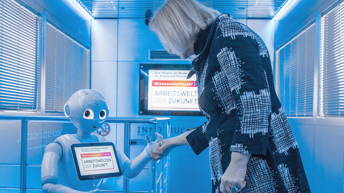Bundesforschungsministerin Johanna Wanka wird im InnoTruck von Roboter Emma begrüßt