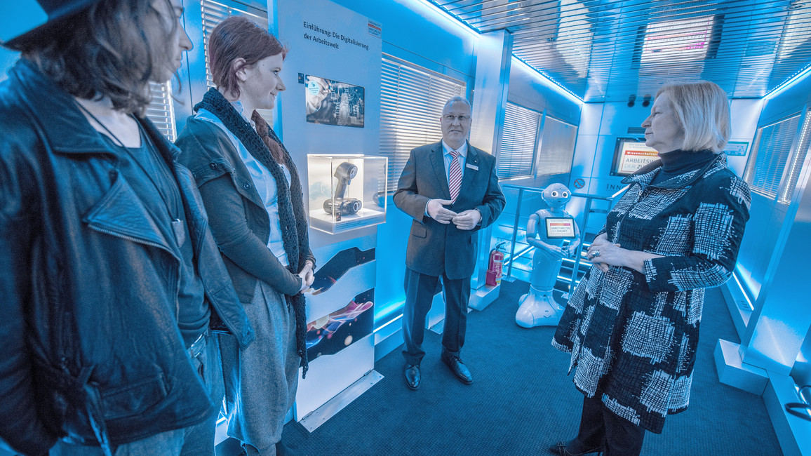 Bundesforschungsministerin Johanna Wanka informiert sich in Begleitung von Auszubildenden der OSZ Bekleidung und Mode Berlin über die neugestaltete Ausstellung des InnoTrucks. Erläutert wird diese von Andreas Jungbluth, wissenschaftlicher Projektleiter InnoTruck.