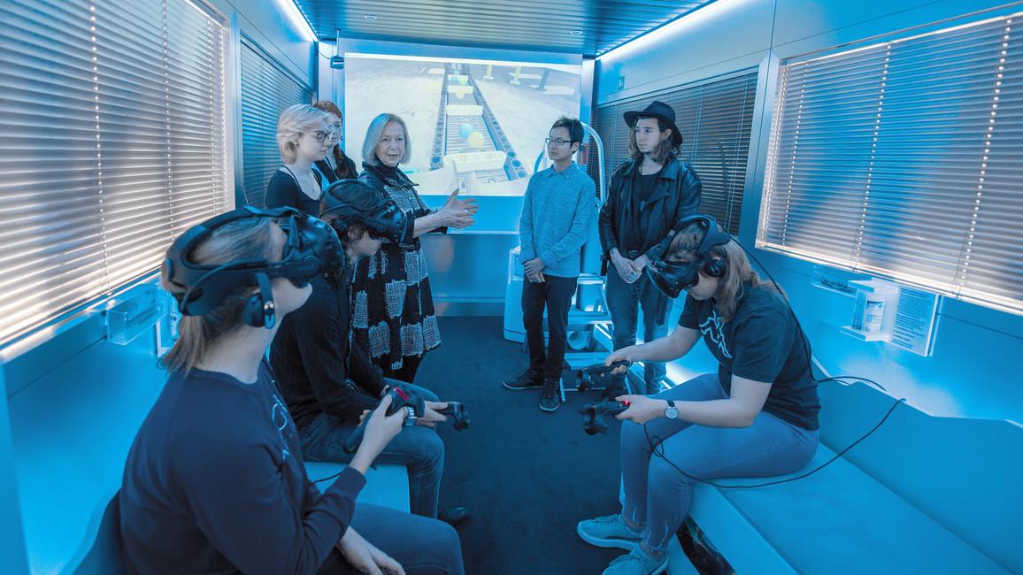 Bundesforschungsministerin Johanna Wanka informiert sich in Begleitung von Auszubildenden über die neugestaltete Ausstellung des InnoTrucks.
