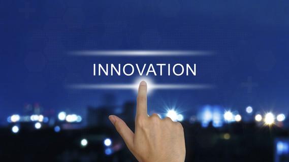Hand drückt Innovationstaste auf einem Bildschirm