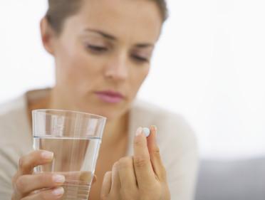 Junge Hausfrau nimmt Tablette zu sich
