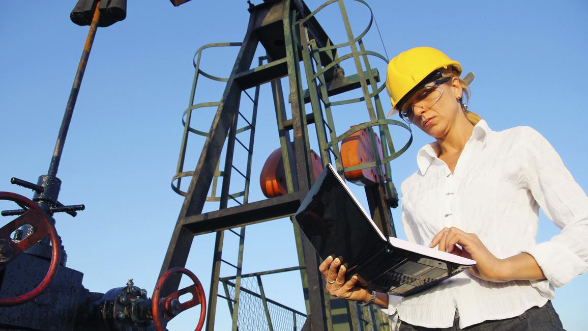 Geschäftsfrau mit einem Laptop an einem Ölfeld