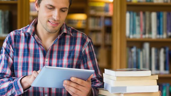 Älterer Student benutzt Tablet PC in der Bilbliothek