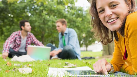 Studentin benutzt Tablet PC, während sie E-Mails im Park liest