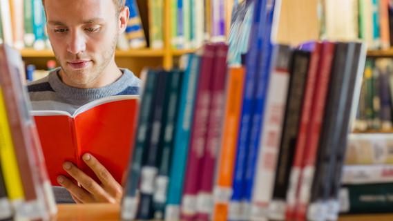 Männlicher Student liest ein Buch in der Bibliothek