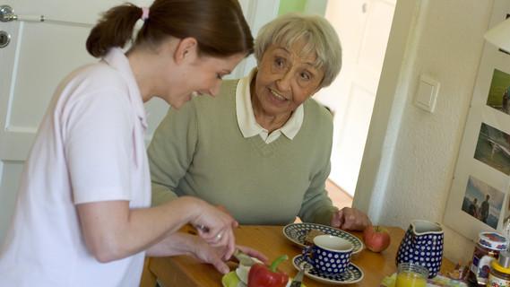 Pflegende Angehörige bereitet Mahlzeit zu für Patientin.