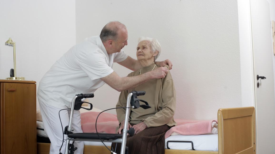 Pfleger hilft älteren Patientin mit Rollator