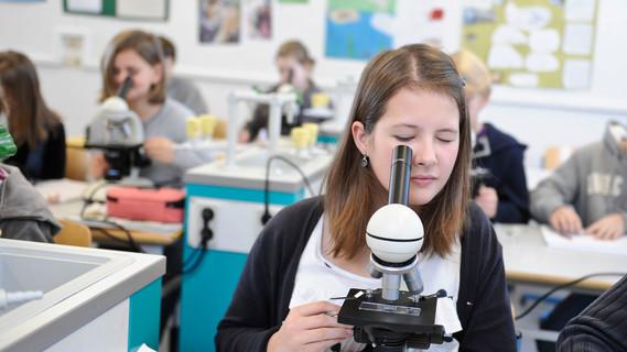 Ein junges Mädchen betrachtet etwas durch ein Mikroskop