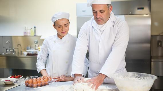 Ein Küchenchef zeigt seinen Auszubildenden wie man einen Kuchenteig zubereitet