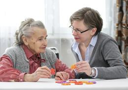 Eine Rentnerin legt mit Ihrer Betreuerin ein Puzzle zusammen
