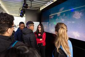 """Der Künstler Jeremy McCain hat für die Ausstellung eine interaktive Kunstaktion kreiert: Auf einem Bildschirm laufen Videos von verschmutzten Stränden und Meeren. Die Besucherinnen und Besucher setzen ein Headset auf, das ihre Gehirnströme vermisst. Erst wenn ihre Gedanken völlig zur Ruhe kommen, springt die Videoinstallation um und zeigt wunderschöne Meeresfilme mit Walen und Walhaien. """"Es ist wirklich schwierig, an gar nichts zu denken, damit die schönen Videos beginnen"""", sagt Julia Schnetzer."""
