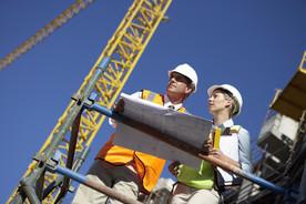Eine Ingenieurin und ein Ingenieur stehen auf einem Gerüst an einem Gebäude