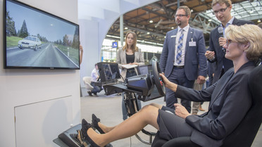 Bundesministerin Anja Karliczek testete bei ihrem Rundgang auf dem BMBF-Stand einen Simulator, der autonomes Fahren erlebbar macht.