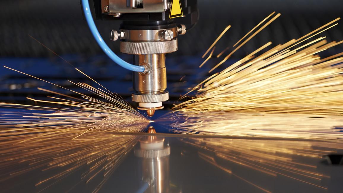 Ein Laser schneidet an Hand einer Schablone eine Metallplatte zurecht