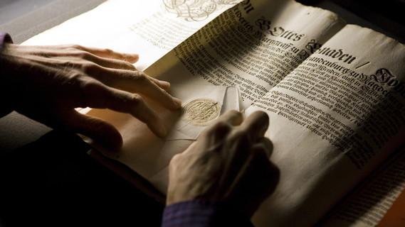 Eine Frau arbeitet an historischen Dokumenten