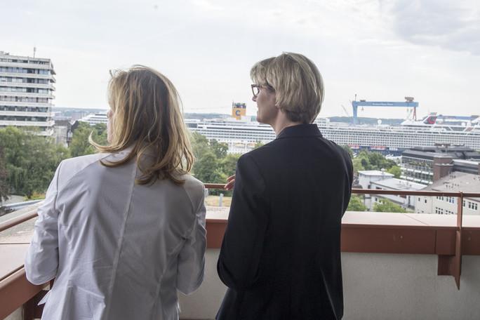 Karin Prien, Bildungsministerin von Schleswig-Holstein, zeigt Bundesministerin Anja Karliczek vom Dach des Ministeriums, die Stadt Kiel
