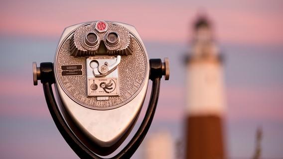 Fernglas mit Leuchtturm im Hintergrund
