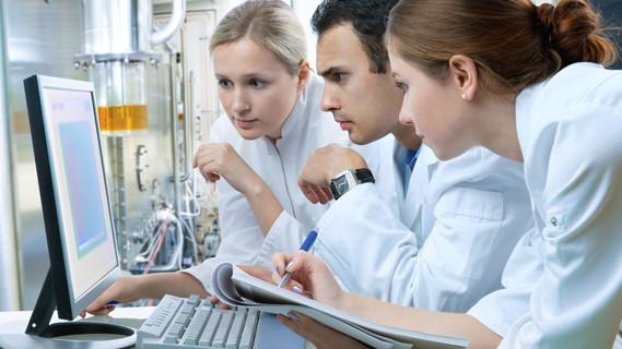 Junge Menschen sitzen gemeinsam vor einem Computer in einem Labor an einer Hochschule