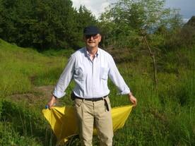 Mit dem Tuch streift Gerhard Dobler über die Vegetation, damit die Zecken sich dort anklammern, so dass sie dann vom Tuch abgesammelt werden können. Er 'simuliert' sozusagen ein Felltier, das vorbei läuft, woran sich die Zecken dann klammern würden. Das ist die übliche Weise Zecken zu sammeln. Man nennt das Verfahren auch 'Flagging'.