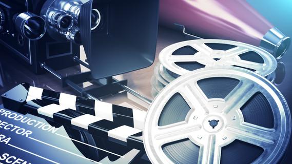 Einzelne Komponenten aus dem Filmbereich. Neben einer Kamera sind auch Filmrollen und ein Brett für die Regieanweisung zu sehen.
