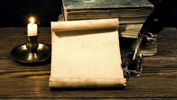 Eine Papierrolle liegt mit einem Buch auf einem Tisch.