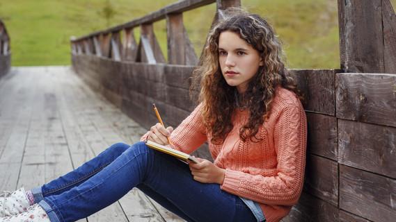 Eine junge Künstlerin sitzt auf einer Brücke und schreibt etwas.