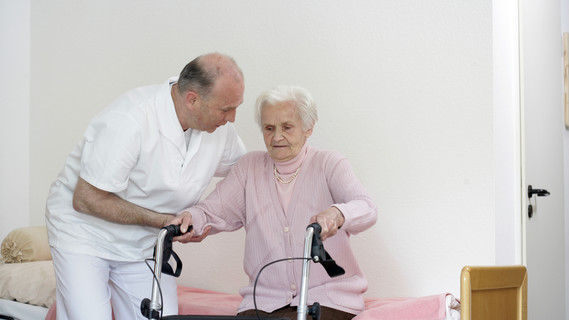 Ein Pfleger hilft einer älteren Dame