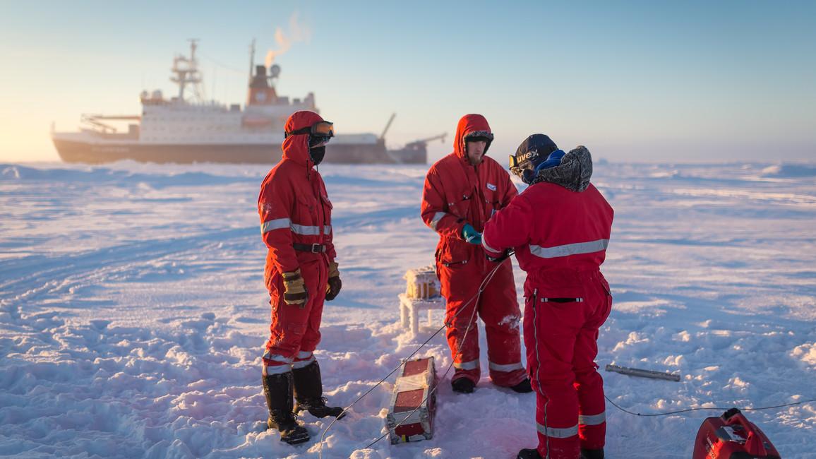 Wissenschaftler des deutschen Alfred-Wegener Institutes bereiten eine automatische Wetterstation auf dem arktischen Meereis vor.