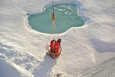 Mit einem großen Korb werden die Wissenschaftler und ihre Ausrüstung vom Schiff auf das Eis transportiert.