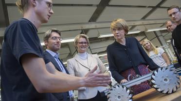 Lucas Riecke (li.), Mechatronik-Auszubildender, stellt Elke Büdenbender (re.), Anja Karliczek (2. vr.) sowie dem Bundestagsabgeordneten Swen Schulz das Projekt einer Fahrzeugsteuerung vor.