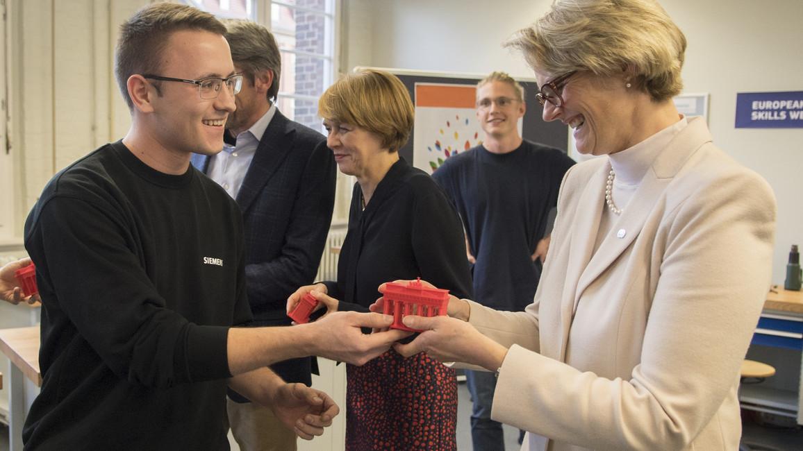 Zur Erinnerung erhält Bundesministerin Anja Karlizek ein Brandenburger Tor, das mithilfe von 3D-Druck hergestellt wurde.