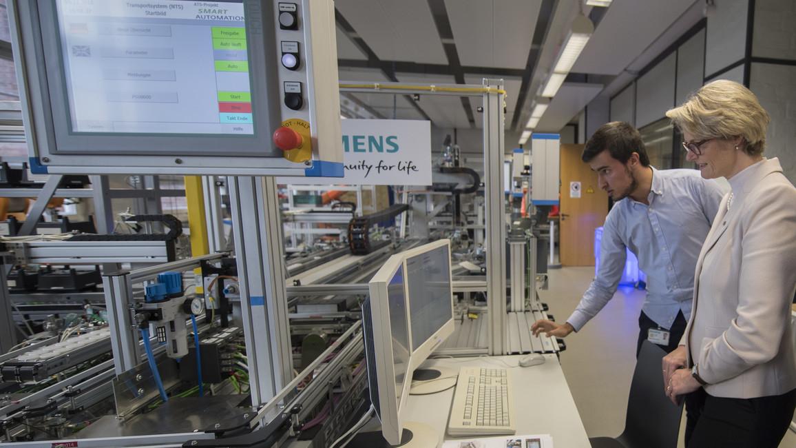 Jaime Garcia del Hoyo, Auszubildender im 3. Lehrjahr aus Spanien, stellt Bundesministerin Anja Karliczek die Arbeitsweise der Smart Automation Anlage vor.