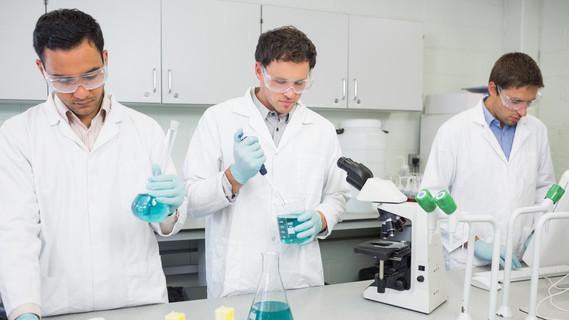Drei Wissenschaftler arbeiten in einem Labor und tragen dabei Schutzbrillen.