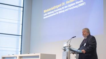 Wie können Lernende Systeme die Wirtschaft und den Alltag revolutionieren? Darüber spricht Herbert Zeisel, Leiter der Abteilung Forschung für den Digitalen Wandel im Bundesforschungsministerium, während eines Impulsvortragesbeim Panel &quotKünstliche Intelligenz konkret&quot.