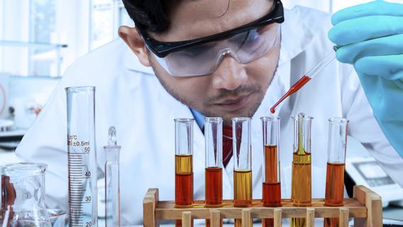 Ein Chemiker experimentiert im Labor und trägt dabei eine Schutzbrille.