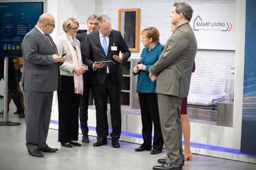 Beim Rundgang mit der Bundeskanzlerin schaut sich Bundesforschungsministerin Anja Karliczek das Exponat &quotSmart Living&quot an.