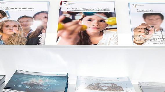Mehrere Broschüren liegen auf einem Regal.