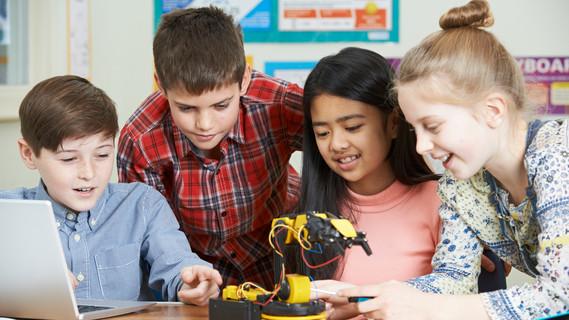 Vier Schüler studieren einen Roboter im Klassenzimmer.
