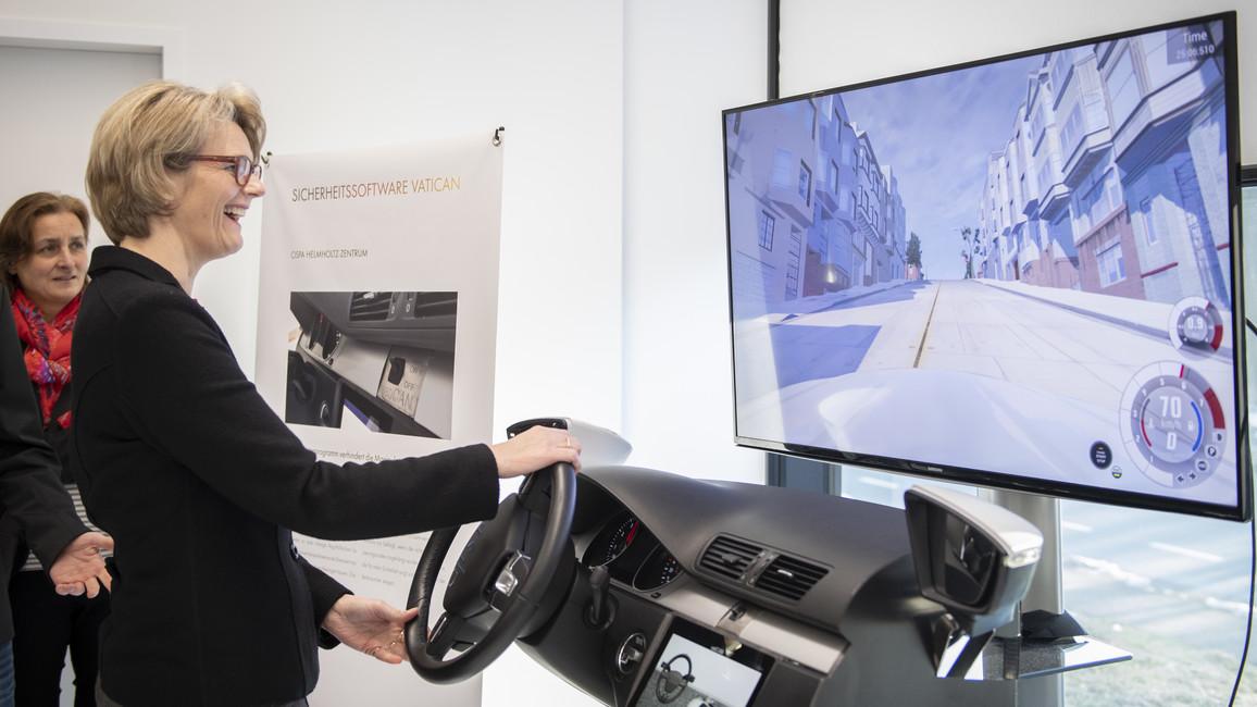 In einem Kfz-Cockpit wird Bundesministerin Anja Karliczek die Funktionsweise der Software VatiCAN demonstriert. Das Projekt wurde 2018 als Ausgezeichneter Ort im Land der Ideen ausgezeichnet.