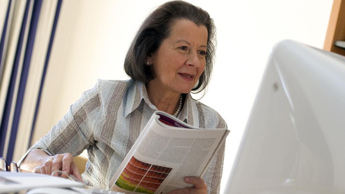 Eine Frau sitzt am Computer und informiert sich