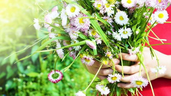 Kind hält einen Blumenstrauß