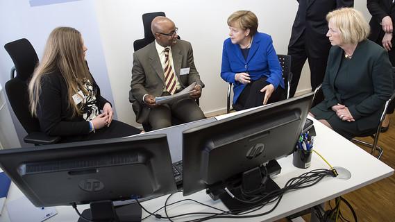 Wanka und Merkel im Gespräch mit einem Buchhalter aus Togo. Sein Berufsabschluss wurde in Deutschland anerkannt.