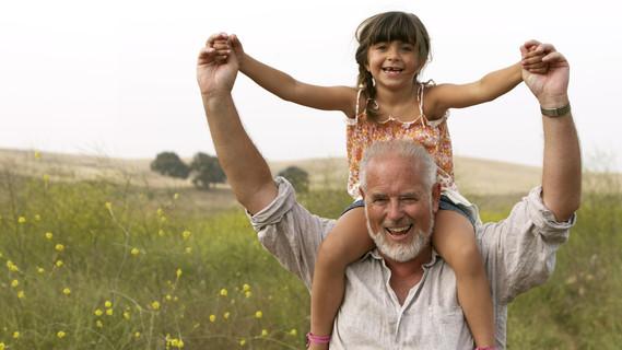 Ein Mädchen sitzt auf den Schultern Ihrer Großvaters.