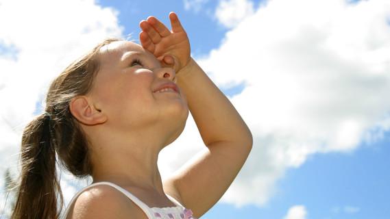 Ein kleines Mädchen schaut in den Himmel.
