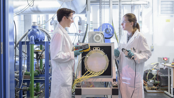 Zwei junge Forscher arbeiten an einer Lithium-Batterie