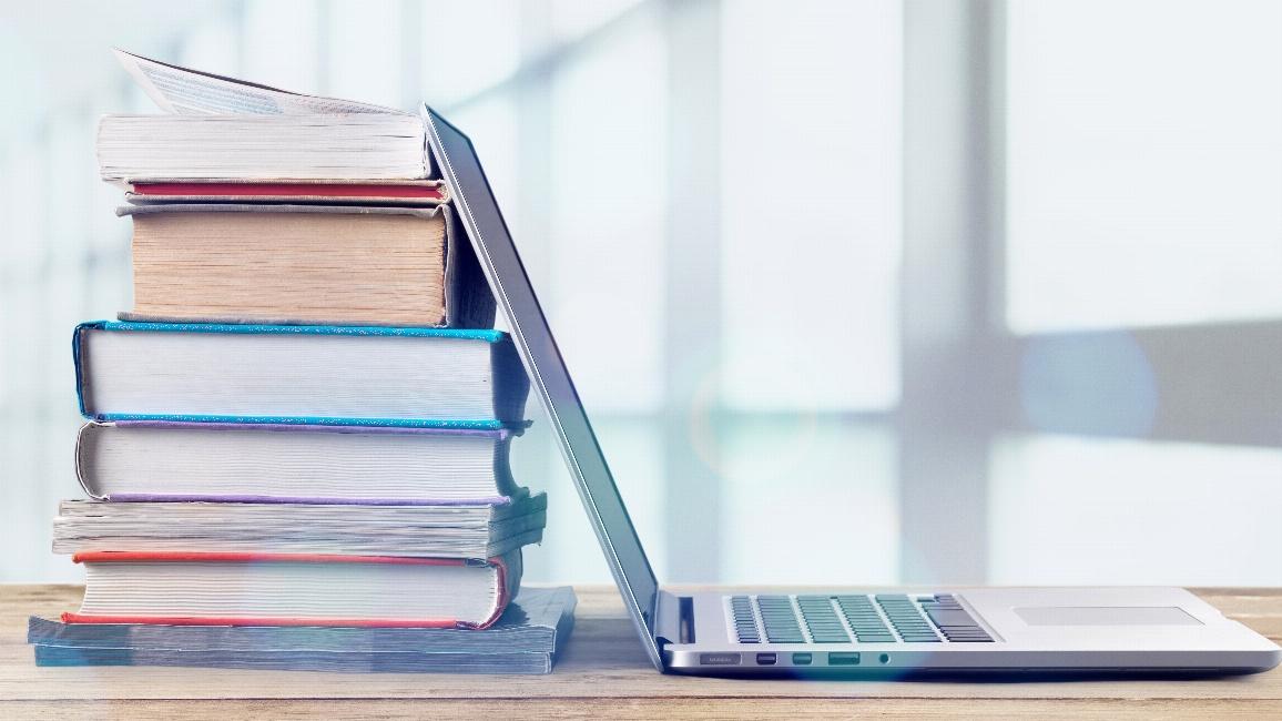 Laptop lehnt an Bücherstapel