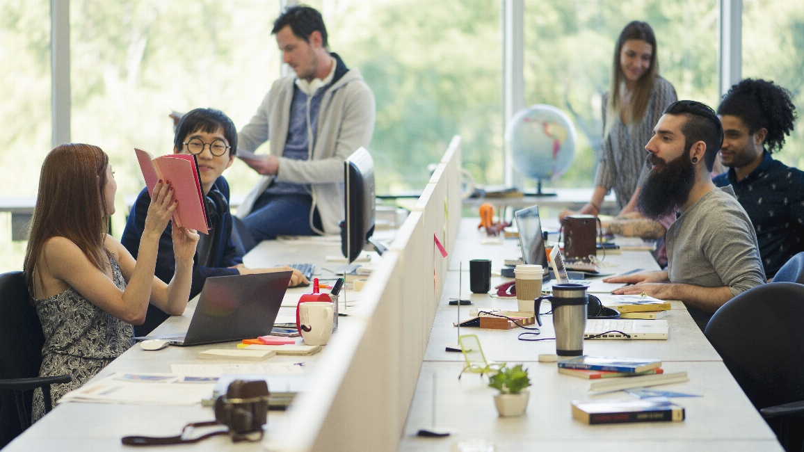 Mehrere Personen sitzen in einem Großraumbüro und diskutieren einen Vorschlag.