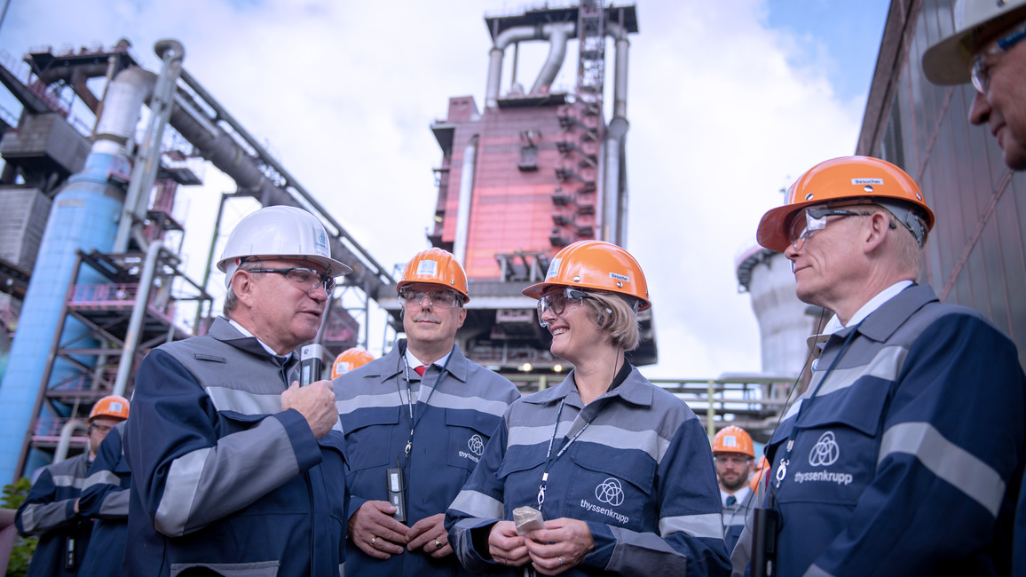 Im Rahmen ihrer Pressereise besucht Anja Karliczek ein Stahlwerk von ThyssenKrupp. Hier steht sie gemeinsam mit einem Betriebsleiter und dem Vorstandsvorsitzenden von ThyssenKrupp, Guido Kerkhoff, vor Hochofen 9.