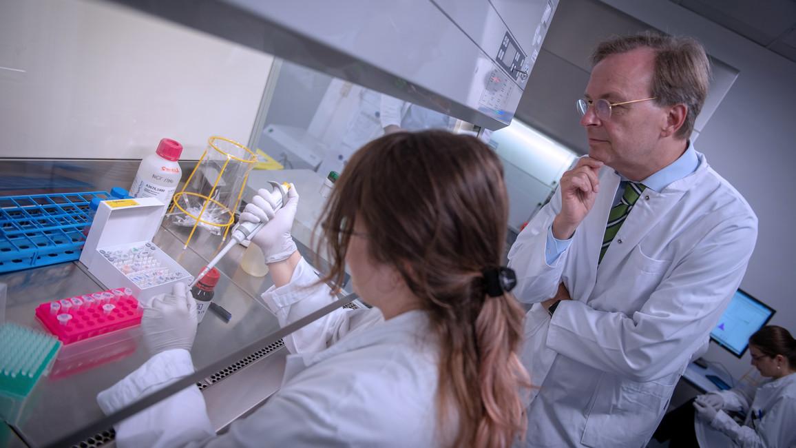 Thomas Rachel lässt sich die Herstellung einer Probe mit Krebs-Zellen für die weitere Untersuchung erläutern.