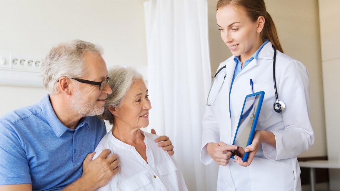 Eine Ärztin erläutert Patienten die Therapie am Tablet.